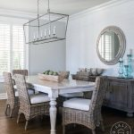 A Darlana Linear Chandelier hangs over a whitewashed dining table surrounded by ...