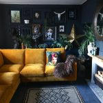 Dark and moody living room with an eclectic gallery wall and mustard velvet sofa...