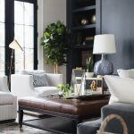 A brown leather tufted ottoman sits on a silver and blue rug between a gray velv...