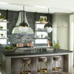 A pair of Hicks Pendants illuminate a taupe kitchen island topped with a honed b...