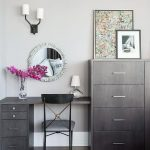 Chic bedroom boasts a gray wash make up vanity and desk combo paired with a blac...