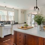 Cottage kitchen with large cherry island topped with a carrara marble illuminate...