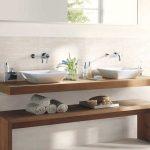 Floating vanity with raised vessel sinks create a sleek, clean, spa-like bathroo...