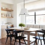 Light wood dining table surrounded by sleek black chairs under a white drum hang...