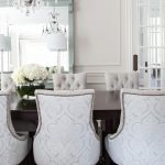 Sophisticated dining room boasts gray damask dining chairs placed around a dark ...