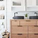 Stone vessel sink on oak vanity in rustic farmhouse bathroom in small cottage ho...